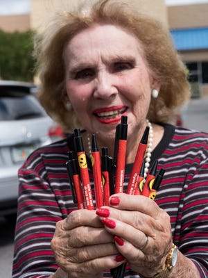 """Retired teacher Virginia McClean shows off the pens she gives out to brighten people's day on Tuesday, April 3, 2018. Over the years, she has given out thousands of the smiley face pens with messages proclaiming """"You Are Wonderful,'' """"Encourage Someone,'' """"Never Give Up'' and """"Keep Hope Alive."""""""