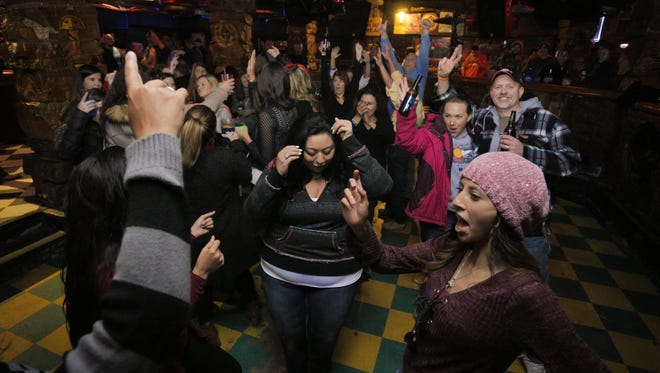 Patrons of Washington's Sports Bar & Grill dance during the establishment's last night in business on April 30, 2016.