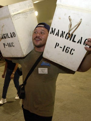 Precint official Greg Quichocho carries ballot boxes into the UOG field house during the 2002 Primary Election.