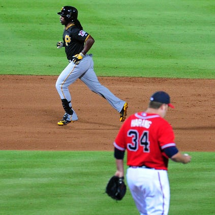 Andrew McCutchen #22 of the Pittsburgh Pirates rounds the bases after hitting a sixth inning solo home run against Aaron Harang #34 of the Atlanta Braves at Turner Field on September 22, 2014 in Atlanta, Georgia.