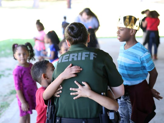 Leon County Sheriff Deputy Cecelia Crego shares a hug with a group of students at Astoria Park, one of four schools that is a part of her patrol as a school resource officer, on Friday, March 2, 2018.