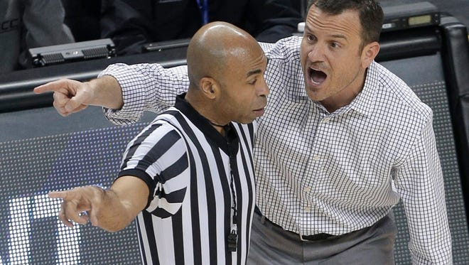 Louisville head coach Jeff Walz, right, argues a call with an official during the first half of an NCAA college basketball game against Georgia Tech in the Atlantic Coast Conference tournament in Greensboro, N.C., Friday, March 4, 2016.