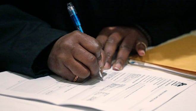 In this April 22, 2015, file photo, a job seeker fills out an application during a National Career Fairs job fair in Chicago. The Labor Department said Thursday, Jan. 14, 2016, applications for jobless aid rose 4,000 to a seasonally adjusted 284,000.