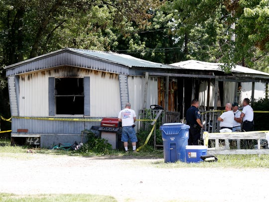 Officials investigate the scene of a mobile home fire