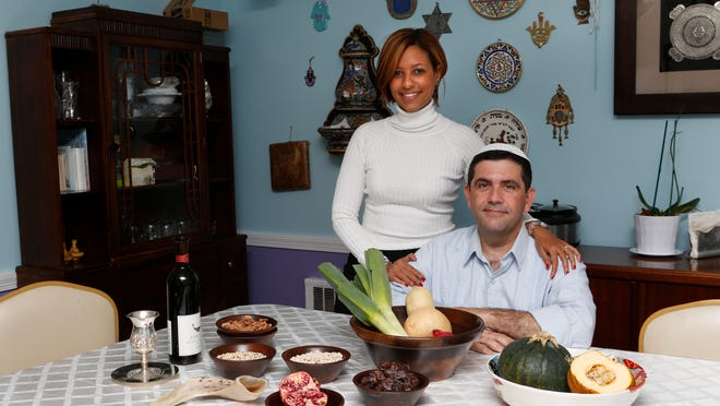 Rabbi Rigoberto Emmanuel Vi?as and his wife Sandra Vi?as are a newly wed Cuban and Dominican couple that put a latin twist on some of the traditional Jewish dishes for the holiday. Rabbi Rigoberto Emmanuel and Sandra Vi?as are photographed with some of the symbolic foods they will eat for Rosh Hashanah, Sept. 12, 2014 in their Yonkers home.