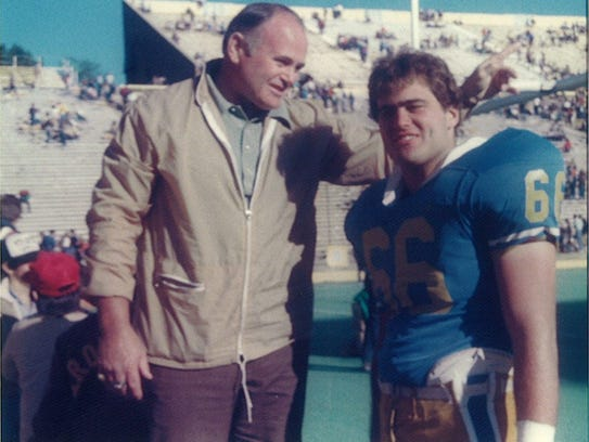 UWF head coach Pete Shinnick, right, talks with his father, Don, following a game during Pete's playing career at the University of Colorado.