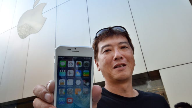 "Apple fan Tetsuya Tamura holds a China made ""iPhone 6"" as he wears a t-shirt with writing translating to ""7 days remaining for iPhone 6 launch"" as he and other fans queue outside an Apple store in Tokyo on September 12, 2014."
