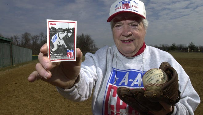 Pat Scott, of Walton, who pitched for the All-American Girls Professional Baseball League's Fort Wayne Daisies, with a baseball card of her during her career and the ball she used in the 1952 pennant win over the Rockford Peaches. The baseball field in Walton Community Park was named for her.