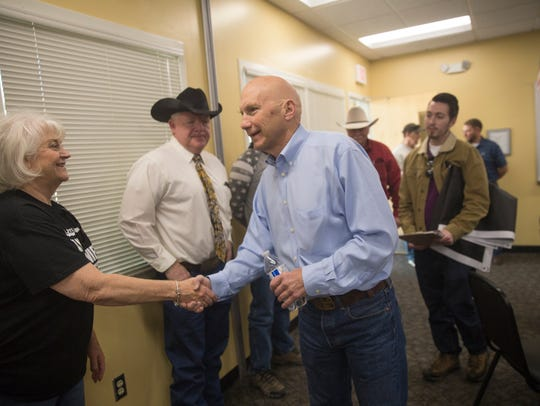 Republican U.S. Senate candidate Mick Rich shakes hands with San Juan County Commissioner Margaret McDaniel, left, and her husband Gary McDaniel on Thursday during Rich's campaign stop at the Aztec Public Library.
