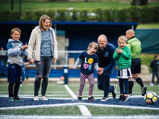 Xavier University men's soccer coach, Andy Fleming, walks onto the field with his family for Devin's Game in 2018. Devin's Game is a fundraiser named after Fleming's daughter who was born with Down Syndrome. Saturday night when Xavier hosts Northwestern will be the 8th edition of Devin's Game.