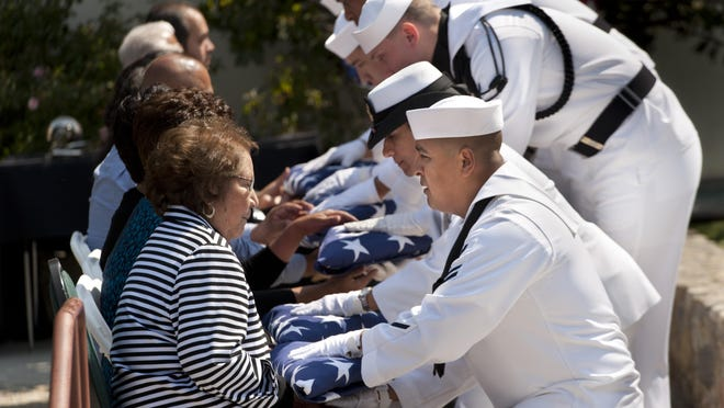 Helen Chavez, widow of Cesar Chavez, accepts a flag from Petty Officer Marco Valovinos as other members of the Navy Operational Support Center in Moreno Valley present flags to her children at the grave of Cesar Chavez during the U.S. Navy ceremony recognizing Cesar Chavez with graveside honors in the Memorial Garden of the Cesar E. Chavez National Monument in Keene in an April 2015 ceremony making the 22nd anniversary of union leader's death.