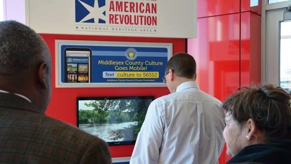 Visitors use a new three-sided kiosk at the Rutgers