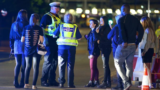 Police and fans close are pictured outside Manchester Arena after at least 19 people were killed following an explosion at the end of an Ariana Grande concert in Manchester, England.