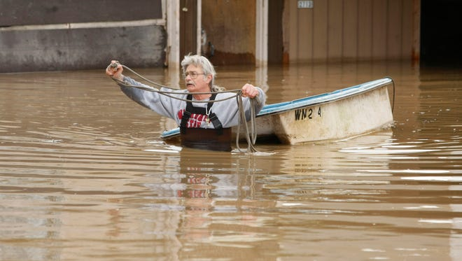 """Buddy Chambers pulls a waterlogged boat from his flooded home in Tacoma, Wash., on Jan. 8, 2009. In early 2009, heavy rains and melting snow caused flooding in parts of Washington, leading to a leak in the earthen abutment of the Howard Hanson Dam. Officials in King County and several cities placed giant sandbags atop downstream levees, erected flood guards around facilities such as a jail and sewage treatment plant, and temporarily relocated the county election office. """"FEMA staff told us, 'We understand why you did what you did, and it was a reasonably prudent thing to protect the public,' """" said Mark Isaacson, King County's wastewater treatment director who at the time led its flood control division. """"But it didn't fall within their definition of imminent flooding."""""""