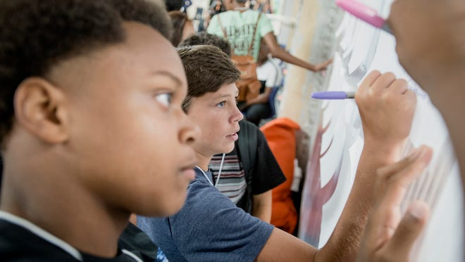 """July 30, 2018 - Students including Jacob Yarbrough, center, and Chioke McKinney, left, sign up for """"Disorientation"""" projects during the first day of class at the new Crosstown High School. After three years in development in Crosstown Concourse the school, which focuses on connecting students to the real world through project-based learning, opened with its first class of 150 ninth grade students. The school plans to gradually increase enrollment to approximately 550 students."""