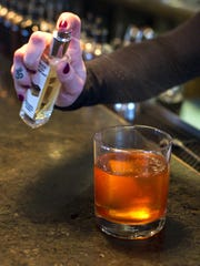 Sydney Stockmann makes a Magician's Boulevard misted with Alice & the Magician's Charred Bourbon Barrel at Pizzeria Verita in Burlington on Monday, March 21, 2016.