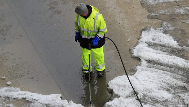 A city worker clears ice Tuesday along the side of Washington Street in downtown Green Bay.