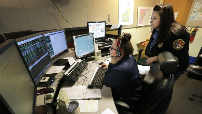 New hire and telecommunicator Calan Stichman, left, learns how to read returns with guidance from certified training officer Heather Van Straten recently at the Outagamie County 911 Communications Center in Appleton. A return is a response they get from the TIME system when they query a person's name for information.