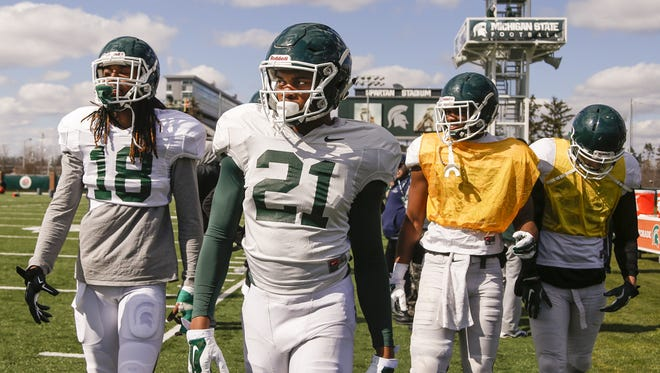 MSU receivers Felton Davis (18), Cam Chambers (21), Edward Barksdale, second from right, and Austin Wolfe, right,  take the field for practice Tuesday in East Lansing.