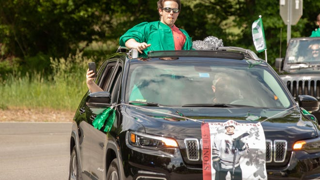 """Sutton High School senior Evan Stone holds a cigar in his mouth during the Class of 2020's Graduation """"Rolling Rally"""" June 4, 2020. Students and families were led by Sutton police and fire through town while the Sutton community cheered from lawns and stoops to support graduates."""