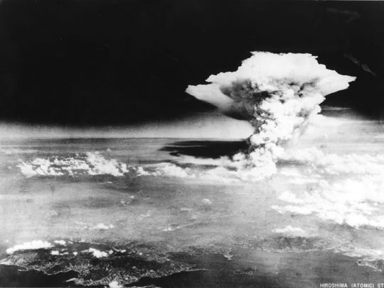 A mushroom cloud from the atomic bomb dropped by B-29 bomber Enola Gay looms over the city of Hiroshima on Aug. 6, 1945.