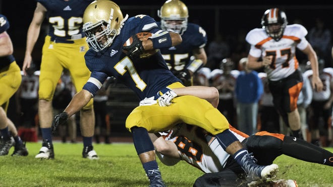 Essex's Jordan Hines (7) is tackled by Middlebury's Skyeler Devlin (82) during the high school football game between the Middlebury Tigers and the Essex Hornets at Essex High School on Friday night Octoer 7, 2016 in Essex.