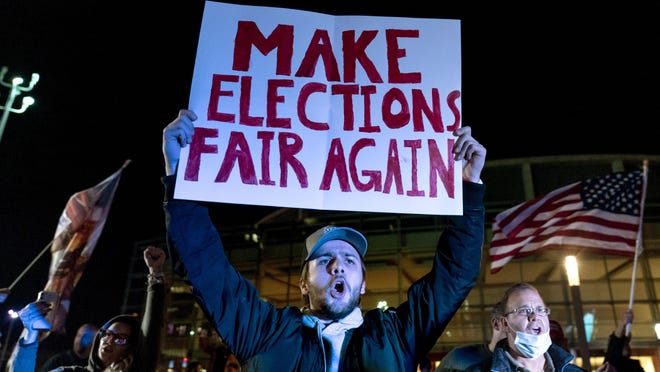 In this Nov. 5, 2020, file photo, Jake Contos, a supporter of President Donald Trump, chants during a protest against the election results outside the central counting board at the TCF Center in Detroit.