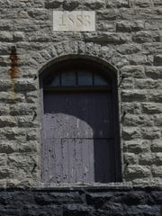 A stone bears the year 1883 above a window Monday, May 22, 2017, on The Granary building. The former a restaurant that is housed in a historic grain and feed mill has been vacant for years.