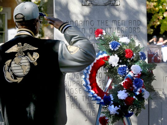 Anthony Knox, Marine veteran, salutes as Taps is played by the Siegel High marching band after placing a wreath at the war memorial monument on the Square in Murfreesboro as part of a  Veterans Day Memorial Service on Wednesday.
