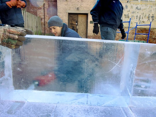 A coworker steadies a 275-pound ice block while Joe