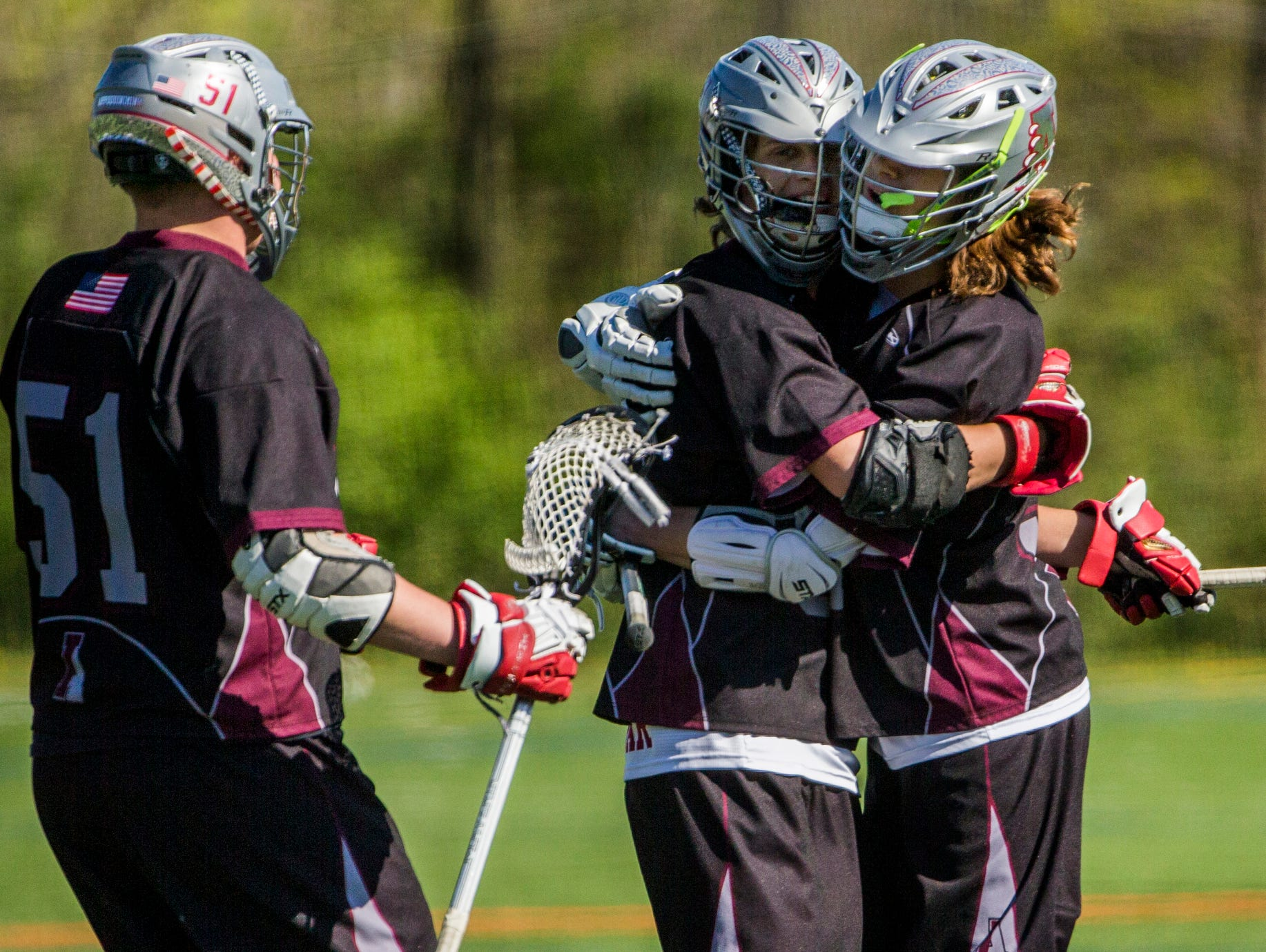 Appoquinimink's John Dunbar (center) gets a hug from teammate Cross Ferrara (right) after scoring a goal in the first quarter of Appoquinimink's 13-12 win over Archmere at Archmere Academy on Wednesday afternoon.