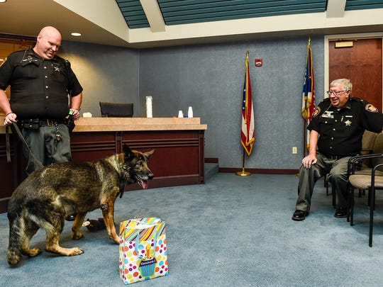 After his retirement ceremony, some treats and new toys, and even a little bit of cake, 'Sig' a K-9 with the Marion County Sheriff's Office, still looks ready to go to work. Until Thursday morning 'Sig' worked with his handler and now owner Deputy DJ Barron (left).