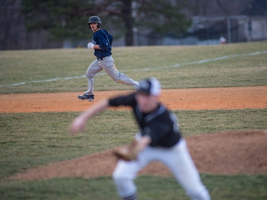 Dallastown's Bryant Holtzapple keeps his eye on the ball as he runs from second to third base during a game last year. Holtzapple returned this season as a the Wildcats' starting catcher.