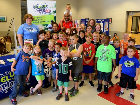 Students in the YMCA Summer program pose with former Tennessee Titan George Wilson at the Seamless Summer Meals Program kickoff, Thursday, June 1, at Trenton Elementary School.