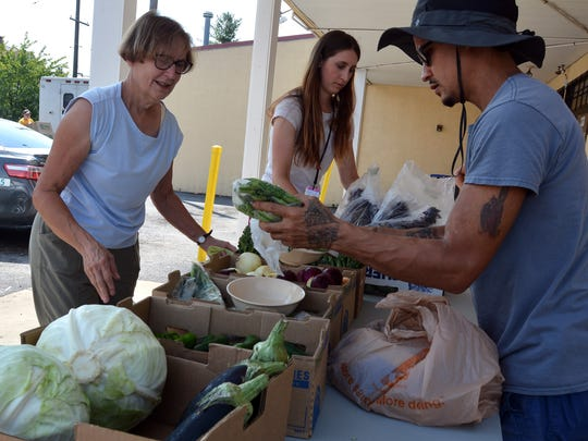 Metta Barbour, left, of York , Paige Nenstiel, community health specialist, and Erick Negron, farm helper at York Fresh Food Farm, set up a produce stand at Pak's Food Market, 750 E. Princess St., Wednesday, Aug. 2, 2017 as part of the Healthy Corner Store Initiative. John A. Pavoncello photo