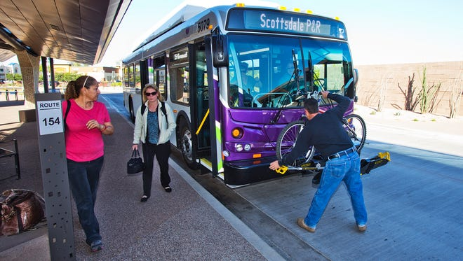 Gary Basil  (right) takes his bike off the front of a bus after taking it from Phoenix to the Valley Metro Park-and-Ride lot at Thunderbird and Scottsdale roads on April 16, 2014.