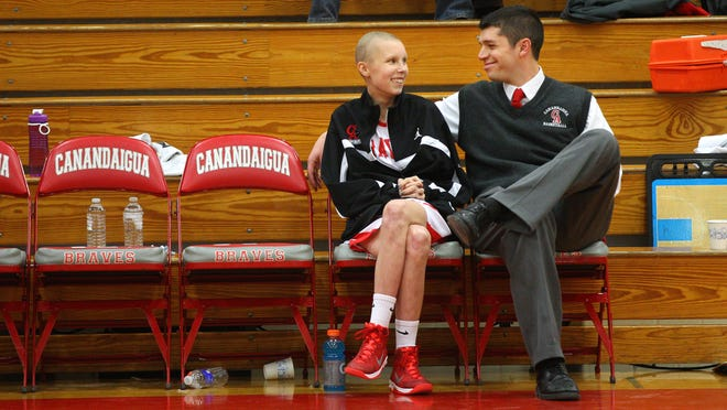 Courtney Wagner takes a moment on the bench with her coach Michael Brennan before her senior night game. Courtney is battling cancer but got to score a basket in Canandaigua's game against Brighton.