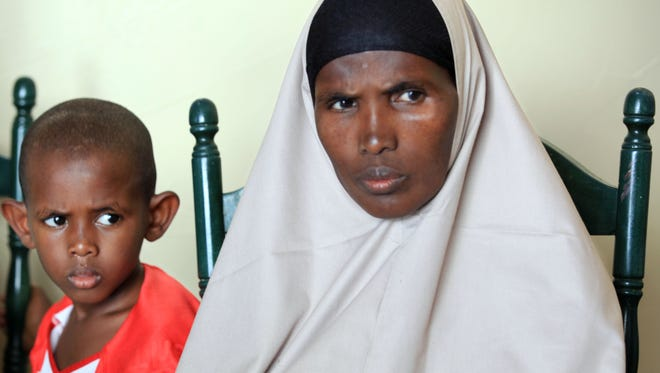 Mumina Hassan Aden, a refugee from Somalia, sits with her 5-year-old son, Suheb Abdi Hujale in their new Rochester home.