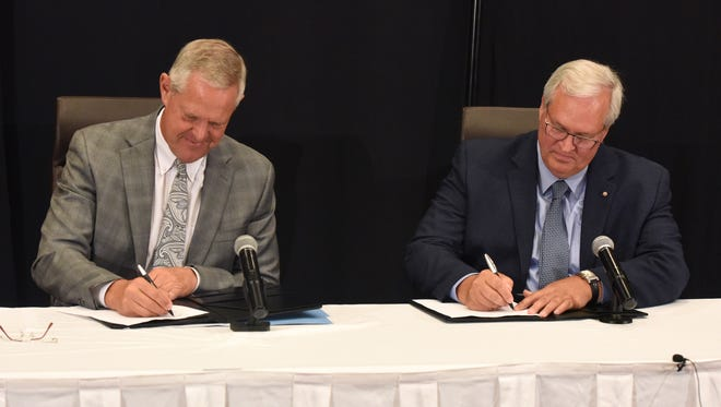 Kelby Krabbenhoft, president and CEO of Sanford Health (left), and David J. Horazdovsky, president and CEO of the Evangelical Lutheran Good Samaritan Society, sign an agreement during a press conference at the Sheraton Sioux Falls & Convention Center in Sioux Falls, S.D. Tuesday, June 26, 2018.