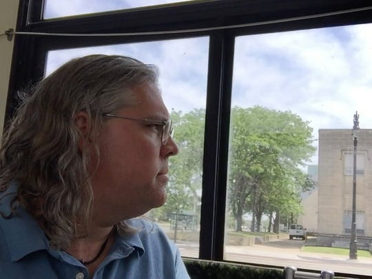 Detroit Free Press reporter Eric D. Lawrence watches looks out the window of a Detroit Department of Transportation bus as he heads towards the DIA for as part of the Free Press' Great QLINE Race on Wednesday, June 28.