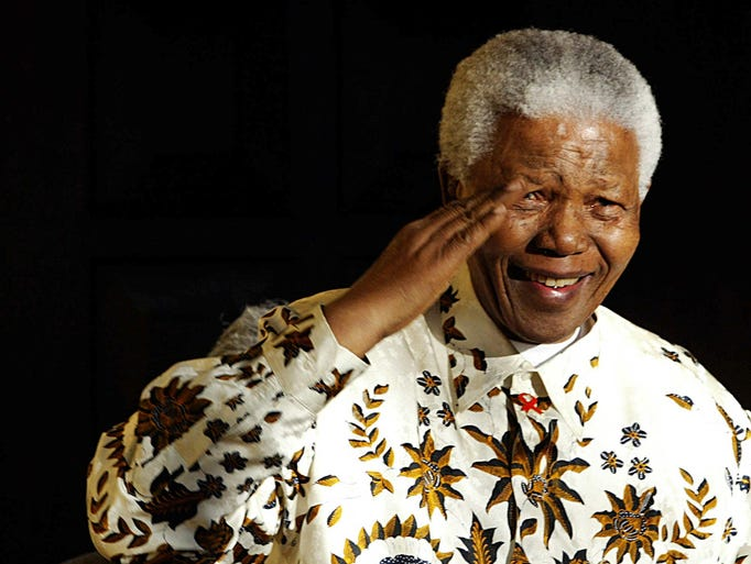 Nelson Mandela salutes the South African military health service band that came to play a specially composed march and happy birthday on his 85th birthday.