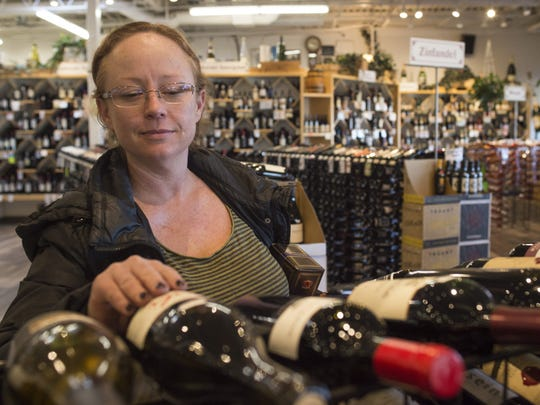 Erica Cowan shops for a bottle of wine at Pringle's on West Drake Road Wednesday, January 27, 2016. Your Choice Colorado aims to bring the idea of full-strength wine and beer to grocery stores around the state.