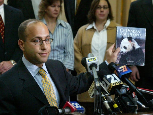 In this file photo, Eric Rothschild, left, an attorney for Pepper Hamilton LLP, holds the textbook that was at the center of controversy as plaintiffs Tammy Kitmiller, center, and Christy Rehm watch at a press conference at the Pennsylvania State Capitol on Dec. 14, 2004.
