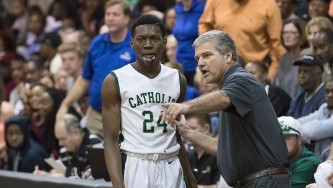 Head coach Jeff Gill gives instructions to DJ McKenzie (24) during the 66-41 Catholic victory over Bolles in the Region 1-5A final basketball game at Catholic High School on Friday, March 2, 2018.