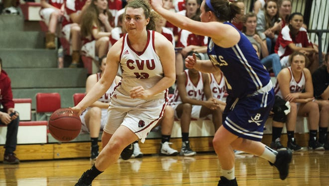 CVU's Marlee Gunn (13) drives to the hoop past Brattleboro's Devin Millerick (2) during the girls basketball game between the Brattleboro Colonels and Champlain Valley Union Redhawks at CVU high school on Thursday night December 22, 2016 in Hinesburg.