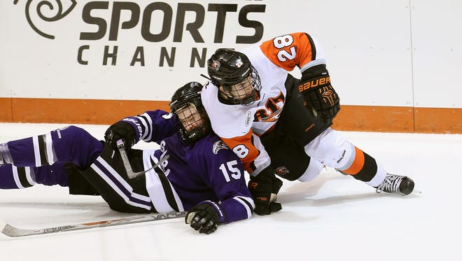 In this file photo, RIT's Mark Logan (28) is dragged down with Niagara's Tanner Lomsnes (15) near the blue line.