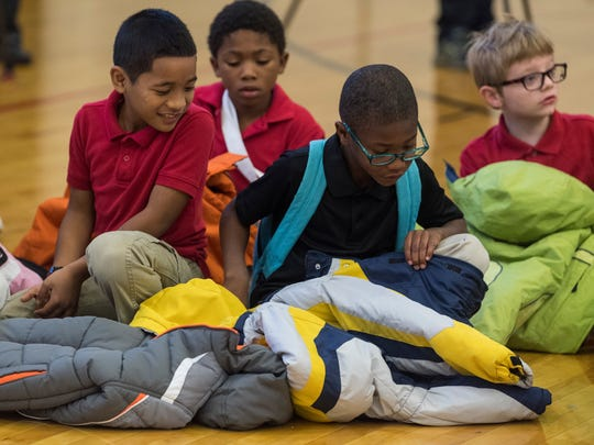 Glenwood Leadership Academy second graders Mackreyner Laneab (left) and Edgar Gibson (right) inspect the coats they were given during the Coat-A-Kid kickoff at their school in Evansville, Ind., Tuesday, Oct. 24, 2017. The students helped film a commercial to inform the community about the coat donation program run by Don's Claytons DCI Fine DryCleaning.
