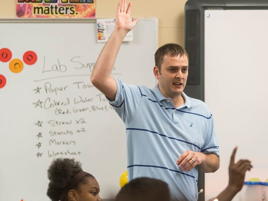 Science teacher George Ennulat III talks to his eighth grade students during a class at Lodge Community School.