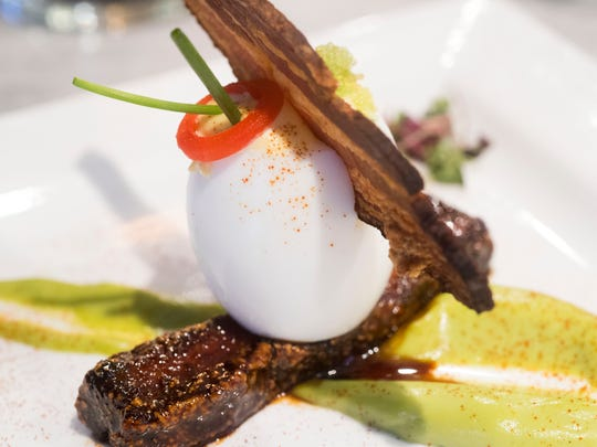 Kitchen 919's Green Eggs and Ham is a deviled duck egg with a slice of Benton's bacon on braised pork belly and avocado hollandaise.