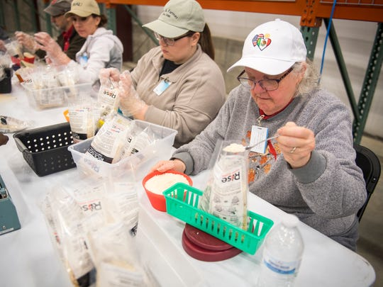 Volunteers pack dehydrated meals into bags for crisis zones around the world at a warehouse on ORAU's south campus in Oak Ridge on Thursday, March 8, 2018.